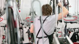 Bicycle storage: mechanic parking a bike in an indoor garage