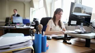 Candid video footage of a female office worker sitting at her desk reading a document on her monitor before reaching for a pen to make some notes.