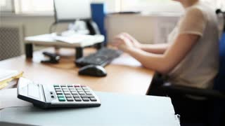 Candid video footage of an anonymous office worker sitting at her desk typing on her computer keyboard. Shallow focus on the foreground calculator.