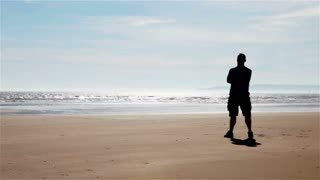 Embracing freedom, solitary man standing on a beach