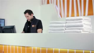 Gym receptionist at front desk with towels