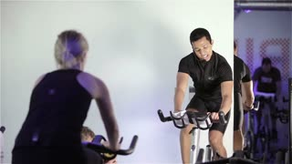 LONDON, UK - 17 NOVEMBER 2011: Candid video footage of a spinning class instructor providing direction and motivation to his class.