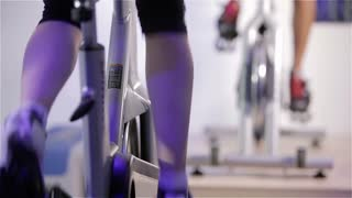 Low angle video footage of an exercise class on spinning cycles or exercise bikes in a commercial gym setting.