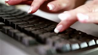 Manicured nails typing on computer keyboard