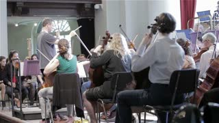 Orchestra rehearsal: conductor and string section