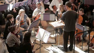 Orchestra rehearsal: conductor talking to musicians