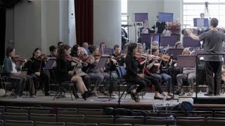 Orchestra rehearsal: slow pan across symphony orchestra