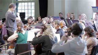 Orchestra rehearsal: string section and conductor