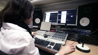 Female sound engineer working in an audio production suite