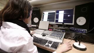 Female sound engineer working alone in a recording studio