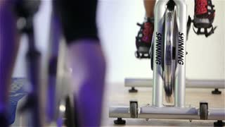 Spinning class: feet pedalling on exercise bikes