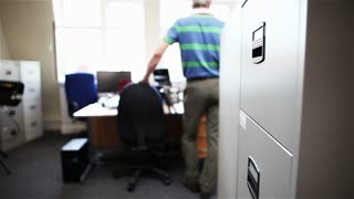 Video footage of a mature, smartly dressed male office worker opening a filing cabinet and placing a folder inside before closing the drawer and leaving the scene.