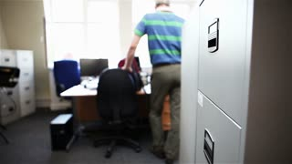 Video footage of an anonymous smartly dressed male office worker opening a filing cabinet to retrieve a file before closing the drawer and exiting the scene.