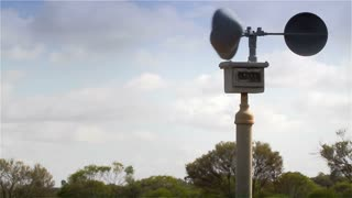 Weather anemometer wind speed gauge spinning in a light breeze set outside against a summer sky background.