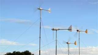 Wind turbine generators spinning quickly set against a blue sky.