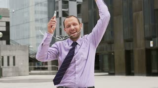 Happy businessman dancing on the square, slow motion shot at 240fps, steadycam shot
