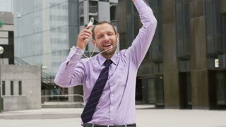 Happy businessman dancing on the square, slow motion shot, steadycam shot