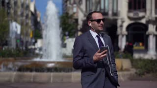 businessman walking near fountain and listening music, slow motion shot at 240fps