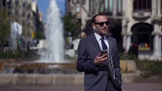 businessman singing and listening music in front of fountain, slow motion shot 60fps