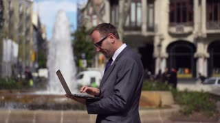 businessman working on laptop close to the fountain, slow motion shot at 240fps