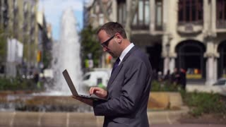 businessman working on laptop close to the fountain, slow motion shot at 60fps