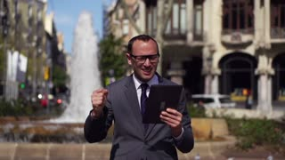 happy businessman with tablet standing in the street, slow motion shot at 240fps