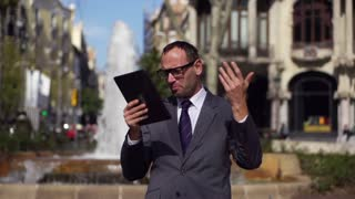 angry businessman with tablet standing in the street, slow motion shot at 240fps