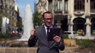 angry businessman with tablet standing in the street, slow motion shot at 60fps