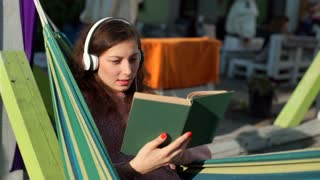 Absorbed girl listening music and reading book while sitting in hammock