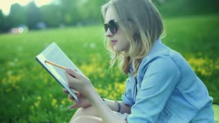 Absorbed girl reading book and studying while sitting on the meadow