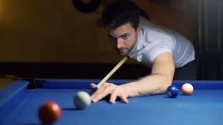Absorbed man playing snooker and smiling to the camera
