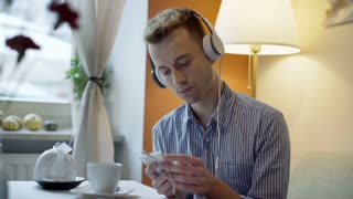 Absorbed man waiting for someone in the cafe while listening music on headphones