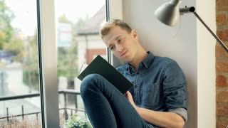 Absorbed, red haired man sitting by the window and reading book