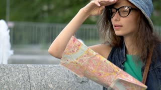 Absorbed tourist reading map next to fountain, steadycam shot, slow motion shot