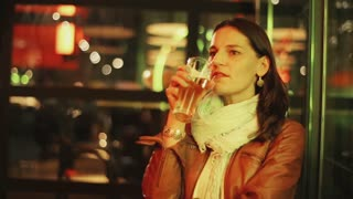 Alone woman drinking beer in pub at night and waiting for someone