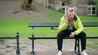 Angry boy talking on cellphone in the park