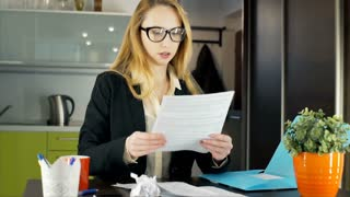 Angry businesswoman destroys papers and looks to the camera, steadycam shot