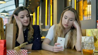 Angry girl checking her smartphone and telling something to her friend, steady