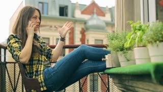 Angry girl sitting on balcony and talking on the phone