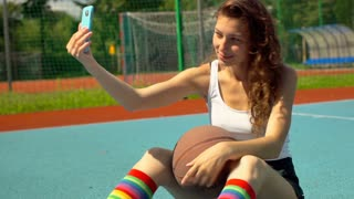 Athletic girl doing selfie with ball on smartphone while sitting on sports field