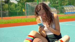 Athletic girl sitting on the sports field and browsing internet on smartphone