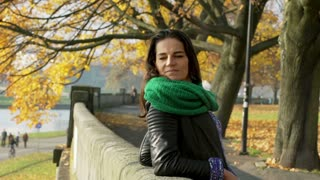 Attractive woman relaxing in the autumnal park