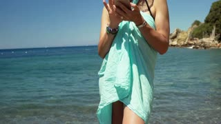 Attractive woman smiling to the camera while standing next to the sea, steadycam