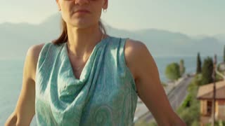 Attractive woman standing next to the sea and looking to the camera, steadycam s