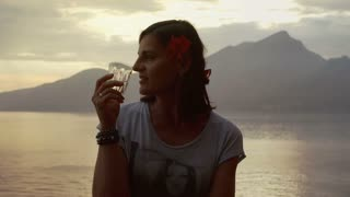 Attractive woman with flower drinking water and standing next to the sea