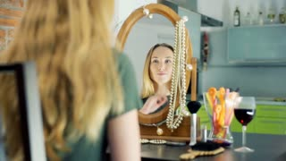 Beautiful, blonde girl checking her appearance in the mirror