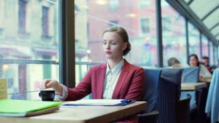 Beautiful businesswoman drinking coffee in the cafe and looking thoughtful