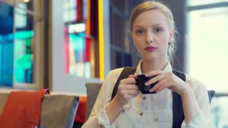 Beautiful businesswoman holding cup of coffee and looking to the camera