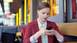 Beautiful businesswoman sitting in the cafe and using smartphone