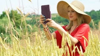 Beautiful girl doing photos on tablet while standing in the grain field